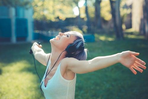 Une femme qui écoute de la musique à bras ouverts