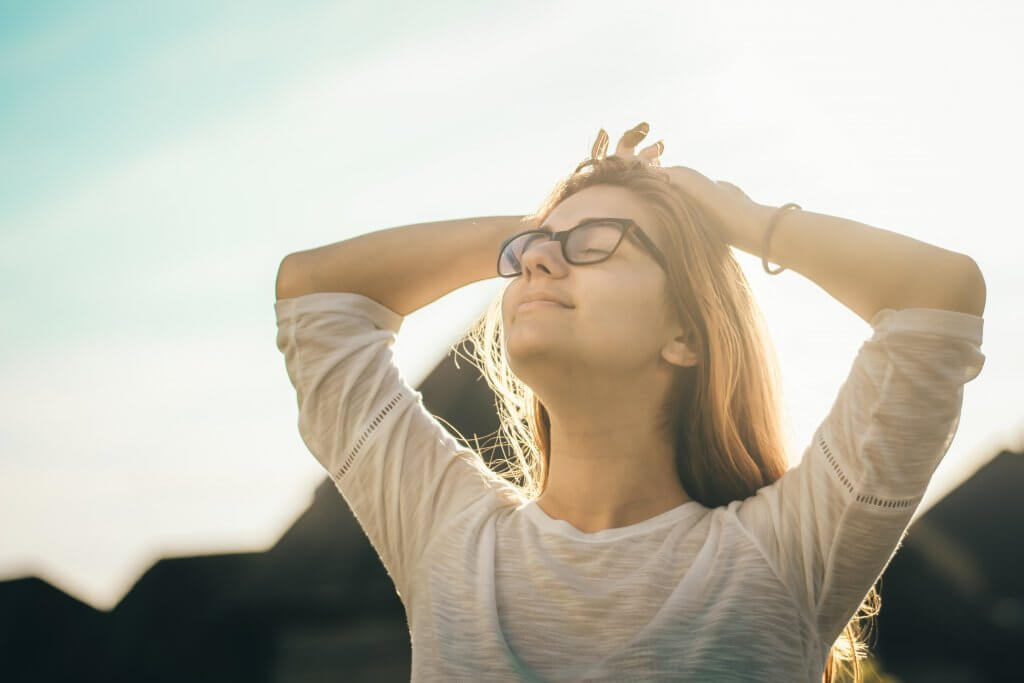 Une femme aux yeux fermés qui pratique l'optimisme