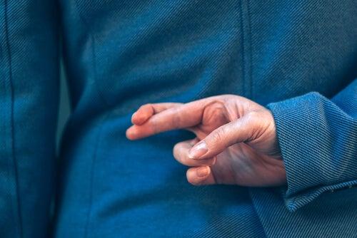 Une femme croise les doigts en mentant pour représenter les mensonges bleus