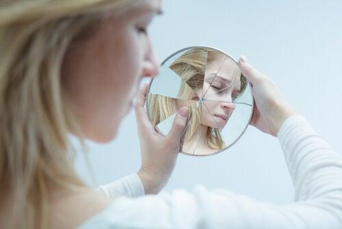 Femme se regardant dans un miroir brisé