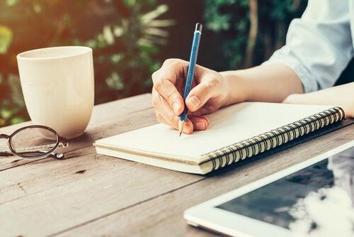 Une femme note ses objectifs dans son carnet