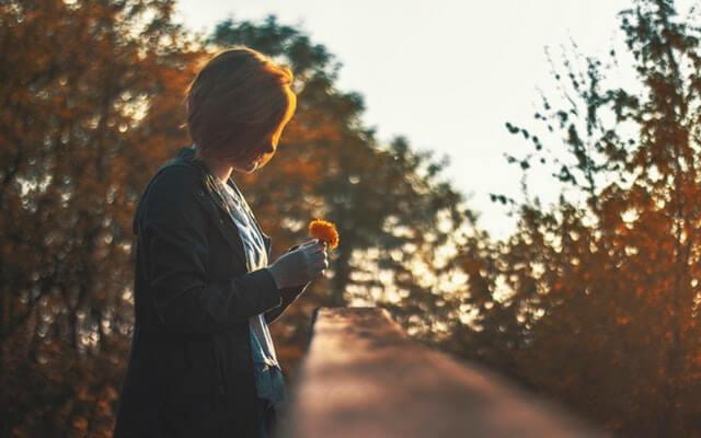 Femme seule regardant une fleur