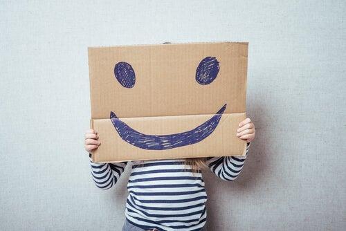 Enfant avec un carton sur lequel est dessiné un visage heureux