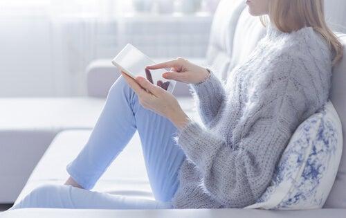 Femme avec une tablette sur le canapé